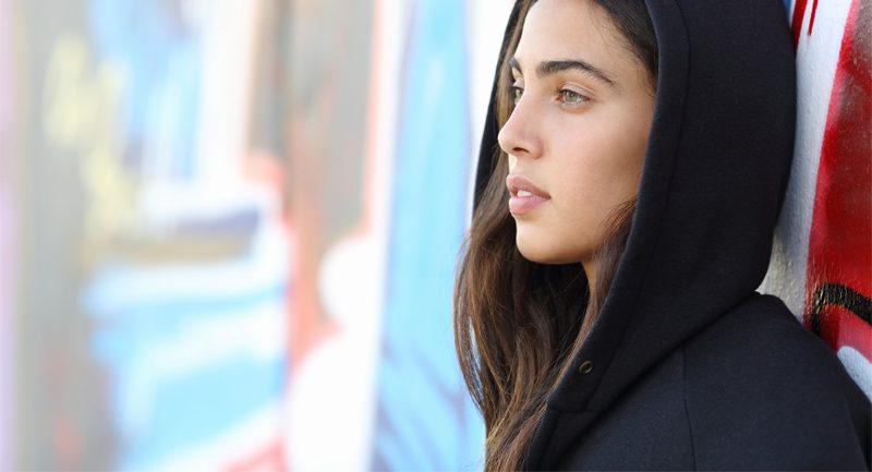 Teenage girl hood up leaning against wall