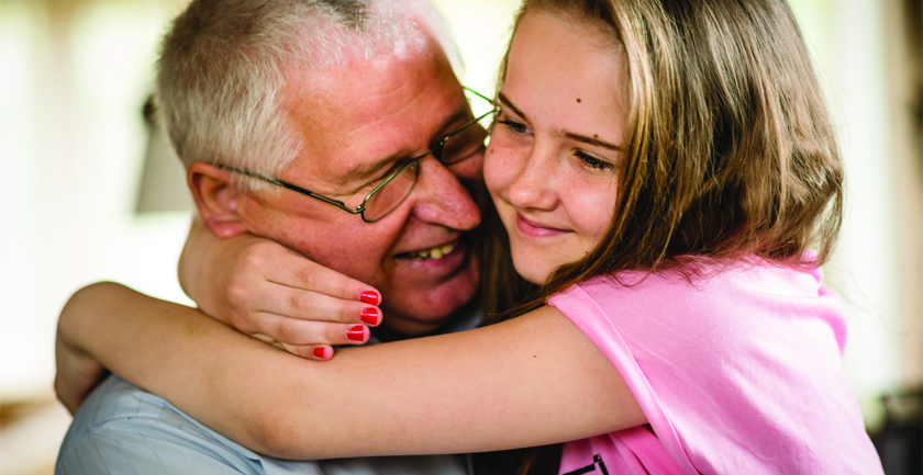 Young girl in pink top hugging smiling man