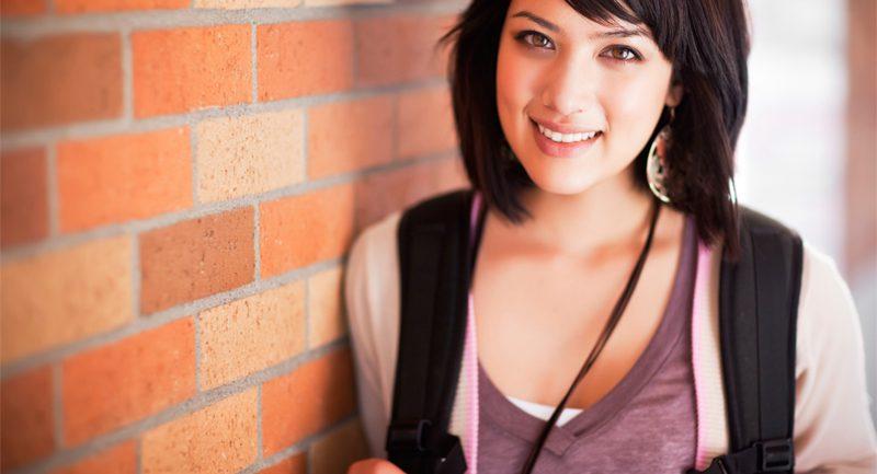 Teenage girl against brick wall