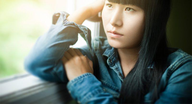 Teenage girl leaning against window