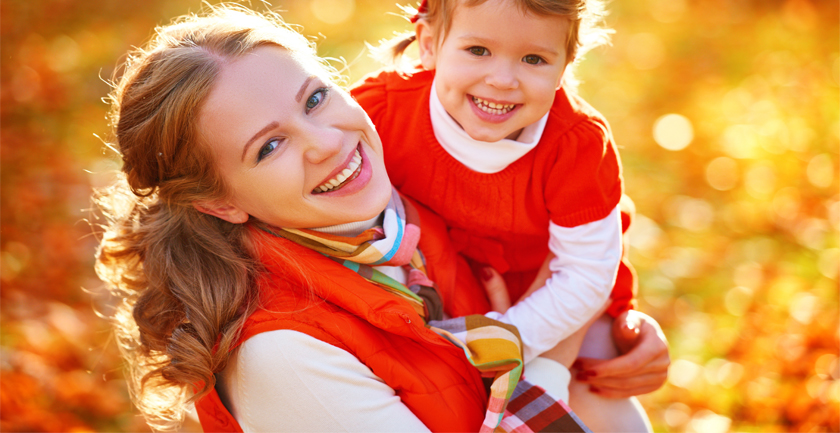 Woman holding young smiling girl