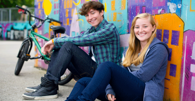 teen-girl-and-boy-sitting-against-a-graffitti-wall