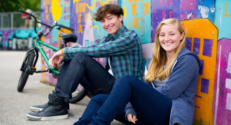 teen-girl-and-boy-sitting-against-a-graffitti-wall
