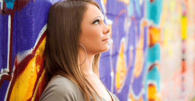 teenage-girl-leaning-on-wall-and-looking-up