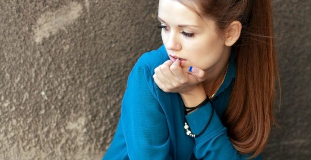 girl-in-a-blue-shirt-sitting-against-a-concrete-wall-picture-id465043902