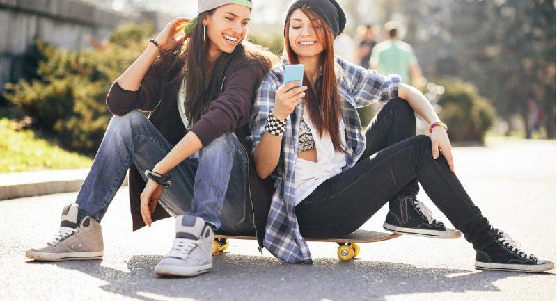 teenage-girls-with-smart-phone-and-skateboard