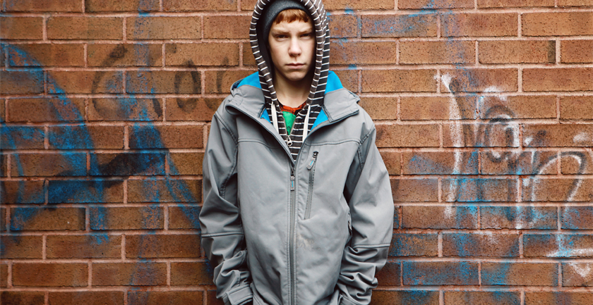 Teenage boy wearing grey jacket and striped hood standing against wall