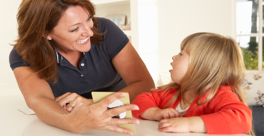 Young girl being shown card by smiling woman
