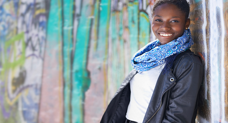 Teenage girl smiling leaning against wall