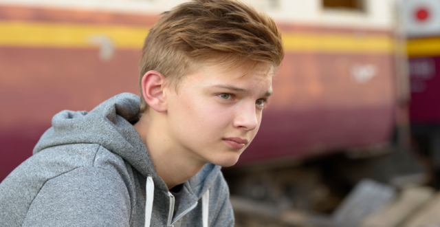 Teenage boy wearing grey hooded top