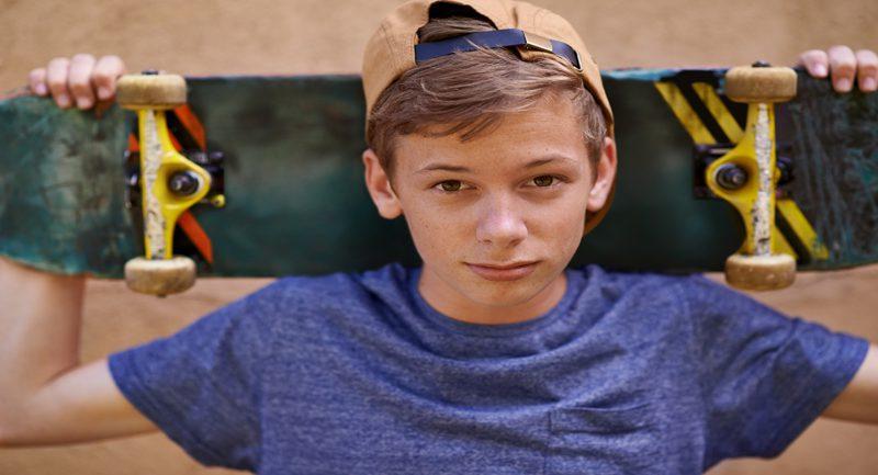 Teenage boy holding skateboard on shoulders