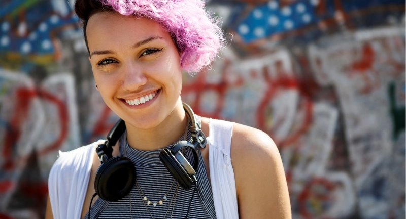 smiling-young-hipster-girl-posing-against-graffiti-wall