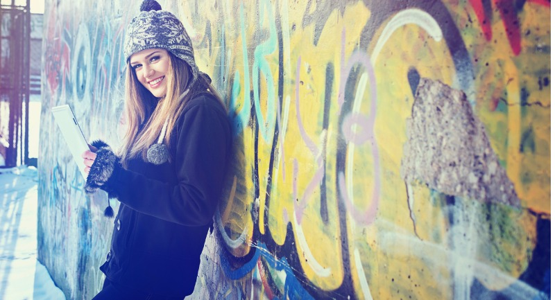 Smiling teenage girl with tablet against graffiti wall