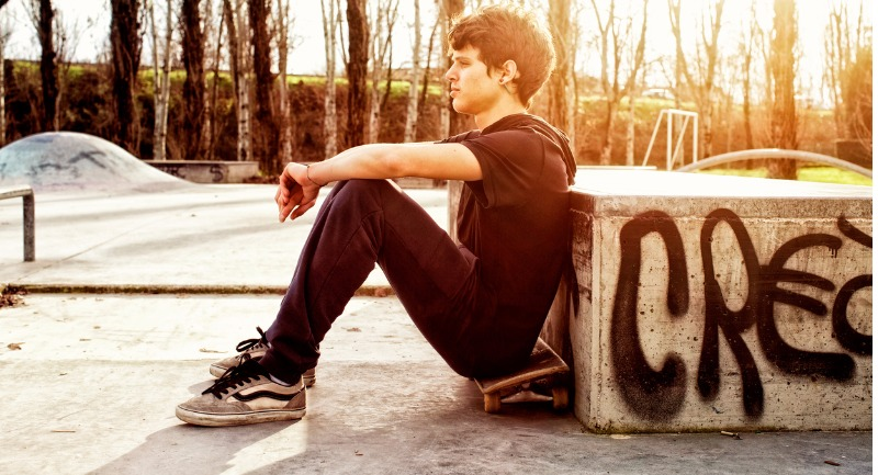 Young skateboarder sitting on skateboard