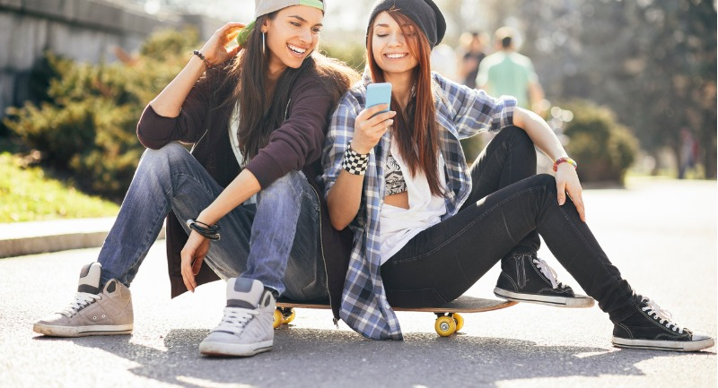 teenage-girls-with-smart-phone-and-skateboard