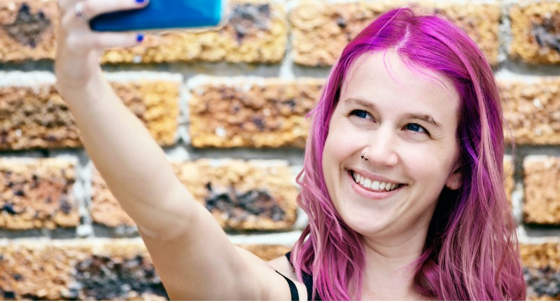 laughing-young-woman-taking-selfie-of-her-magentapink-hair