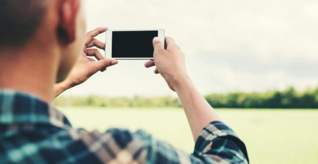 young-hipster-man-using-smartphone-taking-the-landscape-photography