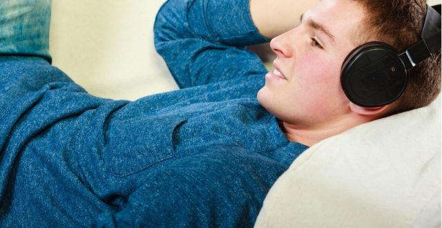 young-man-with-headphones-lying-on-couch-picture