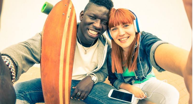 hipster-multiracial-couple-in-love-taking-selfie-with-longboard